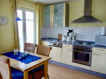 Küchenzeile mit Esstisch und Zugang zum Balkon
