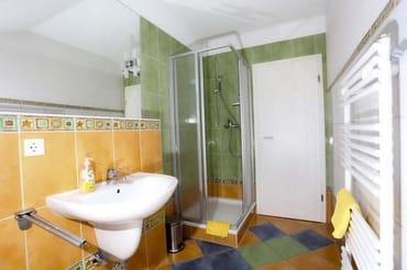 Blick in das farbenfrohe Bad mit Dusche