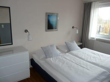 Schlafzimmer mit Doppelbett (1,80m x 2m), Kommode, Kleiderschrank, Blick in den Garten