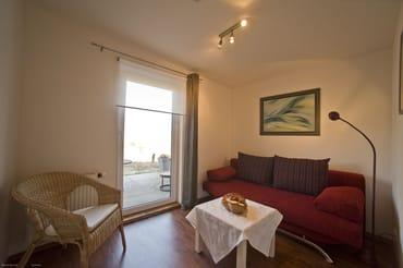zweites kleines Wohnzimmer mit Couch (Aufbettungsmöglichkeit, Liegefläche 1,40 m x 1,90 m), Zugang zur Terrasse mit Blick zur Ostsee in Richtung Kap Arkona
