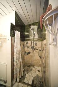 In Marmor gefasster, ebenerdiger Duschbereich mit Regenschauerdusche