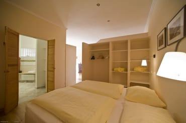Schlafbereich mit Doppelbett (Boxspringbett mit 2 orthopädischen Matratzen 0,90 m x 2 m), integrierter Kleiderschrank