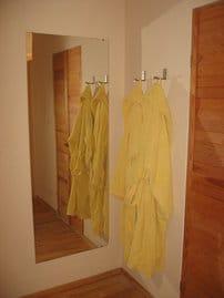 Detail im Schlafbereich: großer Spiegel, Haken für Morgen- oder Bademantel, rechts Tür zum Badezimmer