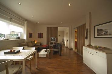 Modern eingerichteter Wohnraum mit Sitzecke (Aufbettungsmöglichkeit, Liegefläche  1,40 m x 1,90 m), SAT-TV/Radio/CD, im Hintergrund Schiebetür mit Durchgang zum Schlafzimmer