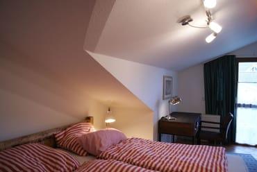 Das Schlafzimmer mit Schreibtisch und Zugang zum Ostbalkon.