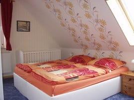 Schlafraum mit Doppelbett und Babybett