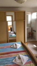Schlafzimmer mit 3 Betten und Blick ins Bad