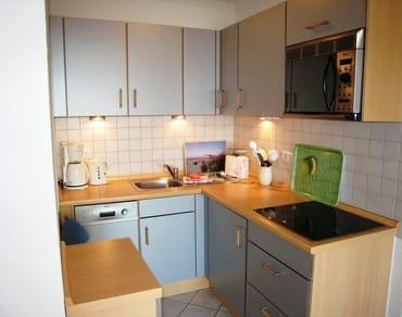 Blick in den gut ausgestatteten Küchenbereich mit Geschirrspüler, Mikrowelle & vielen E-Geräten