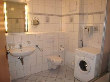 Blick ins großzügige Bad mit Münzwaschmaschine, Fön und Kosmetikspiegel.