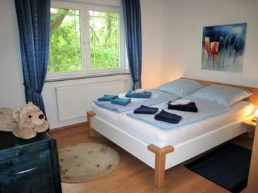 Blick in eines der beiden Schlafzimmer, beide mit Doppelbett (Laminat, getrennte Matratzen, Insektenschutzgitter )