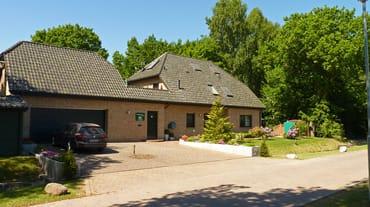 Haus am Wald - Frontansicht mit Parkbereich und Fahrrad-Abstellraum am linken Bildrand