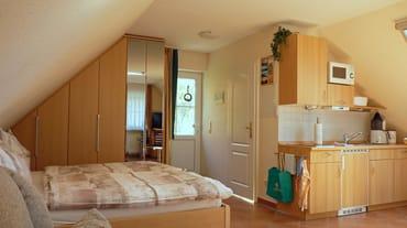 Haupt- und Badeingang (rechts) mit Blick vom Wohn-/Schlafbereich, ausgestattet mit Doppelbett inkl. beids. Nacht- und Einbauschranken, vollst. gefliest mit Fußboden- und Wandheizung