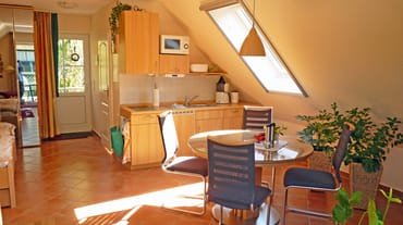 vollst. ausgest. Küchenzeile mit Kühlschrank, 2-Platten Ceran-Kochfeld, Mikrowelle, Kaffeemasch., Toaster und Küchenradio, der Essbereich mit ausziehbarem Tisch bietet ausreichend Platz für 4-6 Pers.