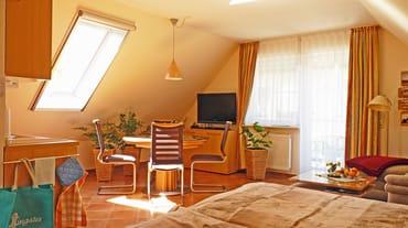 Blick vom Schlaf- in den großzügigen, hellen und mit Sideboards möblierten Wohnbereich, Zugang zum Balkon, Wand-LCD Flachbildschirm (90° schwenkbar), alle Dachfenster mit Jalousie und Insektenrollo