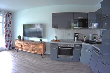 komplett eingerichtete Küchenzeile und großer Flachbildschirm im Hintergrund