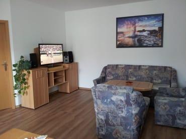 Das Wohnzimmer mit Essbereich ist mit einem großen Fernseher und einer CD-Anlage ausgestattet.