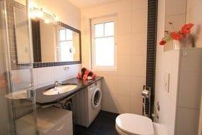 Badezimmer mit bodengleicher Dusche und Waschmaschine