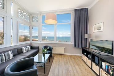 Der Wohnbereich befindet sich in der Loggia mit fantastischem Meerblick. Smart-TV und Radio sind ebenfalls vorhanden. Auf der Couch kann aufgebettet werden.