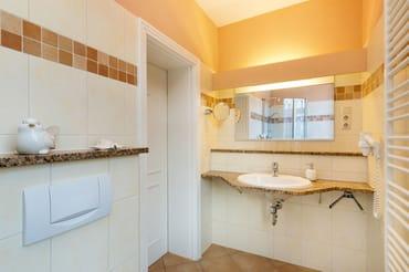 Hier der Blick in das schöne Bad mit großem Waschtisch ...
