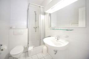 Das weiße Bad mit Dusche und WC.