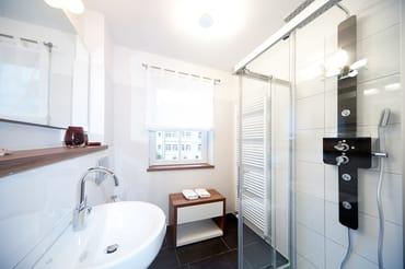 Das Bad mit Wellnessdusche, Waschtisch, WC und Sichtschutzplissee am Fenster. Des weiteren hat die Fewo ein zusätzliches Gäste-WC.