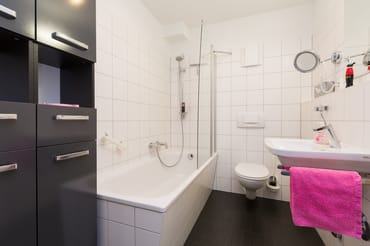 Das Bad hat eine Badewanne mit integrierter Dusche und WC.