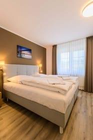 Schlafzimmer mit komfortablen Boxspringbetten und LED-TV