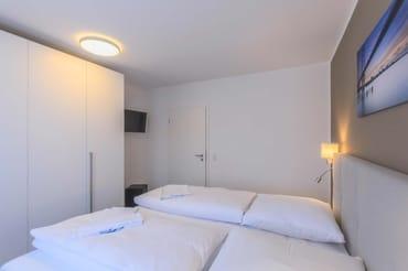 Schlafzimmer mit großen Kleiderschrank und LED-TV