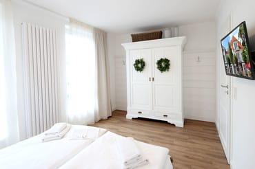 das freundliche Schlafzimmer mit einem Doppelbett, einem großen Kleiderschrank sowie zusätzlichem TV