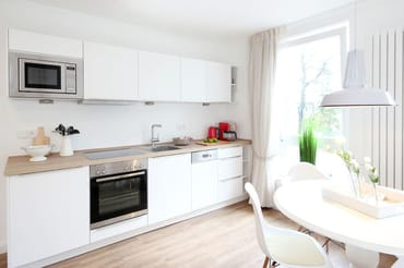 die gut ausgestattete Küchenzeile mit u.a. Geschirrspüler, Backofen, Ceranfeld, Mikrowelle, Kühlschrank und einem davor liegenden separaten Essplatz