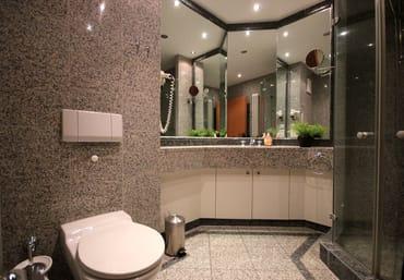 das moderne Badezimmer ist mit Granit gefliest und enthält eine Dusche, WC, Waschtisch und Fußbodenheizung