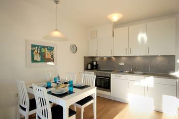 die gut ausgestattete Küchenzeile mit u.a. Geschirrspüler, 2-Platten Herd und mit einem separaten Essplatz im Wohnbereich