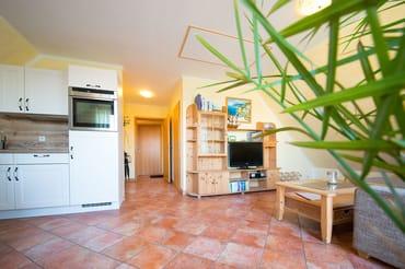 Der kombinierte Wohn- Koch und Essbereich überzeugt mit Relaxsofa, Flat TV, ...