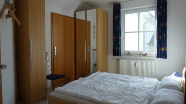 Schlafzimmer 1 mit Schränken und Ganzkörperspiegel sowie Zugang zum Abstellraum