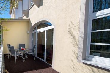 Dieses Foto zeigt die straßenseitig gelegene Terrasse, die vom Wohnzimmer aus betreten wird.