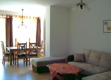 Wohnzimmer mit Schlafcouch und Erker mit Eßecke