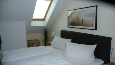 1 Schlafzimmer mit Doppelbett und Bettwäsche
