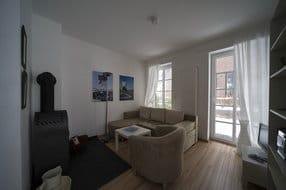 Wohnraum mit Kaminofen, Sat-TV, Stereoanlage, Internetzugang, Bücherregal, Fenstertüren mit Zugang zur eigenen Terrasse mit Gartenmöbeln
