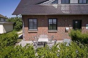 Terrasse mit Gartenmöbeln, große Spiel- und Liegewiese befindet sich hinter Taras' Hus