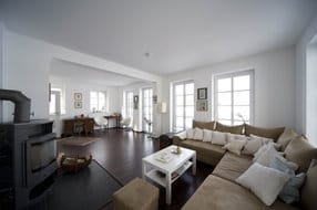 Wohnraum mit Kaminofen, großer Sofabereich, Antiquitäten, Schreibtisch, Sitzplatz, alles in weiß / Makassar-dunkel Farbtönen gehalten, Fenstertüren zur großen Terrasse mit Sitzmuschel und Gartenmöbeln