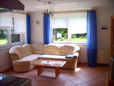 Blick auf die gemütliche Sitzecke im Licht durchflutetem Wohnraum. Links im Bild der Durchgang zur Terrasse mit Gartenmöbeln und Fahrradhäuschen.