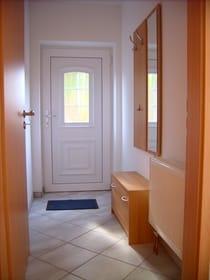 Die Ferienwohnung verfügt über einen eigenen Eingang. Im separaten Flur befindet sich eine Garderobe mit Spiegel und ein Schuhschrank.