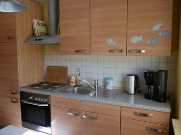 Küchenzeile mit Herd, Backofen, Wasserkocher, Kaffeemaschine sowie genügend Geschirr.