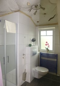 Badezimmer mit Dusche und Handtuchtrockner über Fußbodenheizung
