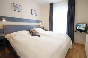 Schlafzimmer mit Doppelbett und Schrank sowie LED-Fernseher mit DVD