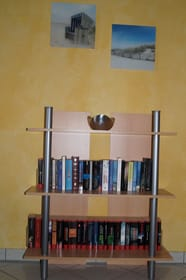 Eine kleine Urlaubsbibliothek steht im Wohnzimmer