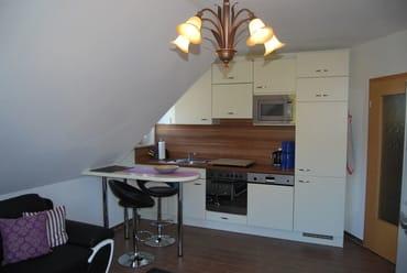 komplett ausgestattete Küchenzeile mit Kochherd, Kühlschrank, Mikrowelle und Geschirrspüler