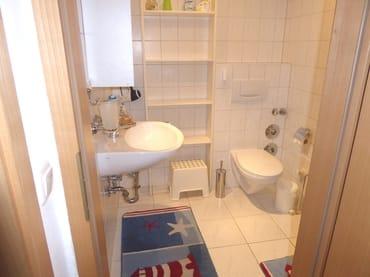 Badezimmer mit Dusche, Fußbodenheizung, großem Regal und Handtuchtrockner