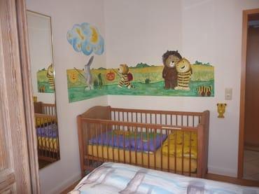 Kinderbett im Elternschlafzimmer mit Janosch-Wandmalerei