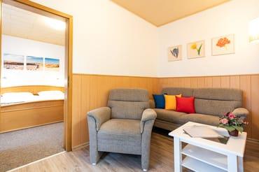 Im Wohnbereich befindet sich eine 2er - Sitzcouch, Sessel, Tisch und TV.